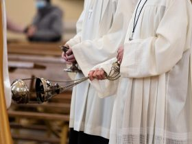 A minister in a white robe holds a censer during Holy Mass