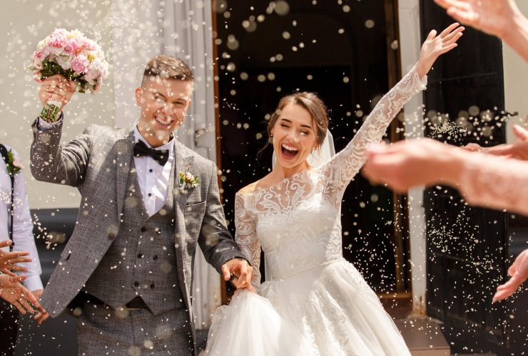 Happy wedding photography of bride and groom at wedding ceremony. Wedding tradition sprinkled with rice and grain